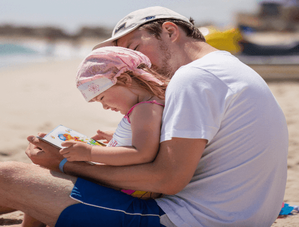 A man reading a book to a child on the beach